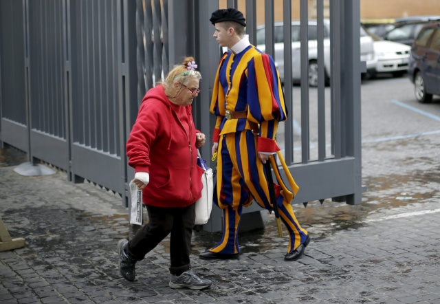 A homeless woman walks past a Swiss guard as she enters the Vatican March 26. (CNS/Reuters)