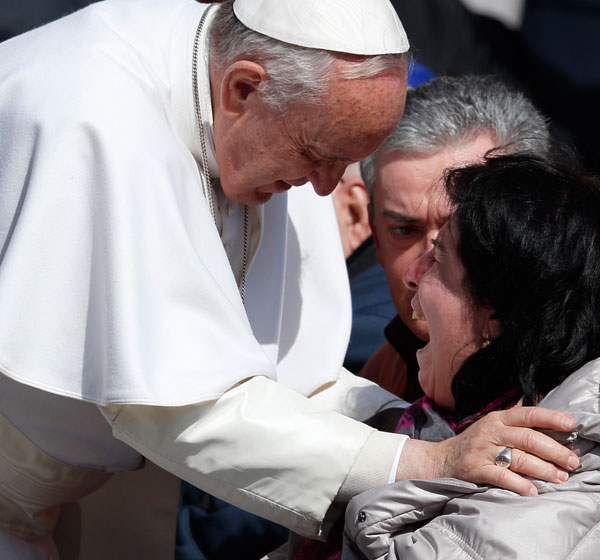 A woman in a wheelchair cries as she meets Pope Francis during his general audience at the Vatican March 18. God's mercy has been a strong theme in the life of the former Jorge Mario Bergoglio. (CNS/Paul Haring)