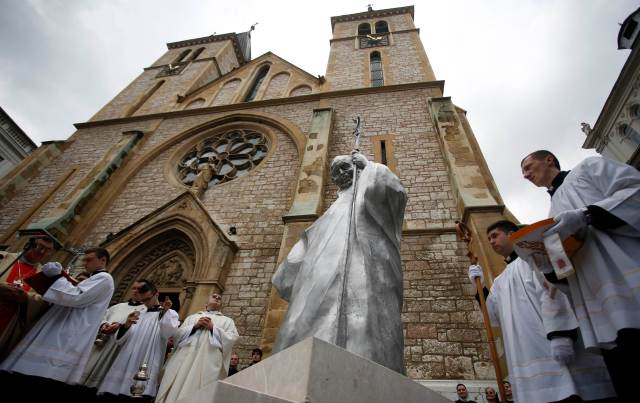 Clergymen stand outside a church during an unveiling ceremony of a statue of St. John Paul II in Sarajevo last year. (CNS/Reuters)