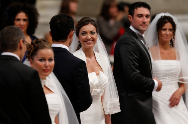 Newly married couples smile after exchanging vows as Pope Francis celebrates the marriage rite for 20 couples in St. Peter's Basilica at the Vatican in 2014. (CNS/Paul Haring)