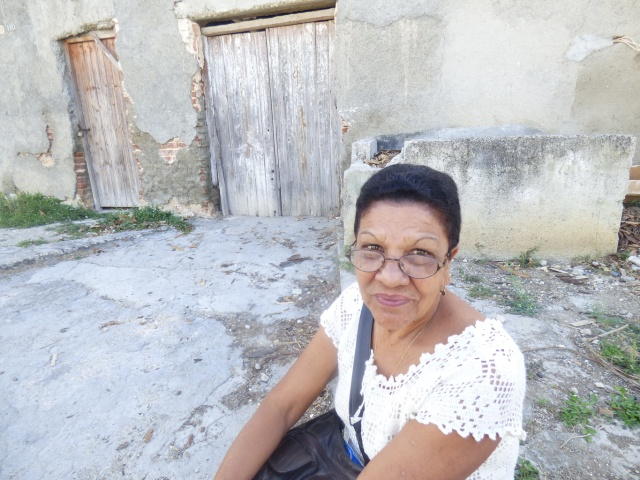 Clementina Torres sits outside her former Catholic parish in Cueto, Cuba. A fixed-up building next door has become the new parish, but the old one is a reminder of a past that was not friendly to Catholics on the island. (CNS/Rhina Guidos)