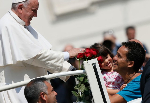 Pope Francis greets family members during his general audience April 15. (CNS/Paul Haring)