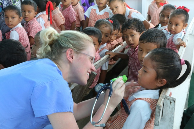 Schoolchildren look on as Taryn Hill, a second-year resident from Austin, Texas, examines a girl at a health clinic in a village in Guyana. (CNS/Bob Roller)