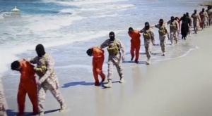 Islamic State militants lead what are said to be Ethiopian Christians along a beach in Libya in this still image from an undated video made available on a social media website April 19.  (CNS/via Reuters TV)