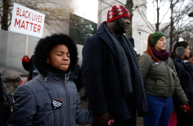 A young marcher closes her eyes as marchers hold hands during a prayer in Washington Dec. 13 at the Justice For All national march calling for changes in the nation's criminal justice system. (CNS/Jim Bourg, Reuters)