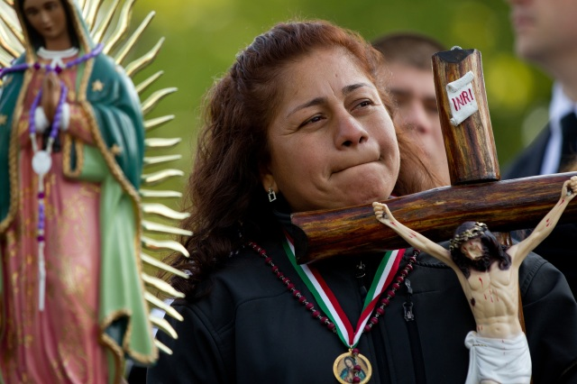 A woman holds a crucifix as people demonstrate against an Arizona immigration law outside the U.S. Supreme Court in 2012. (CNS file/Nancy Wiechec)