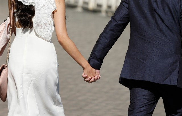 A newly married couple hold hands as they arrive to attend Pope Francis' general audience in St. Peter's Square at the Vatican May 27. (CNS/Paul Haring)
