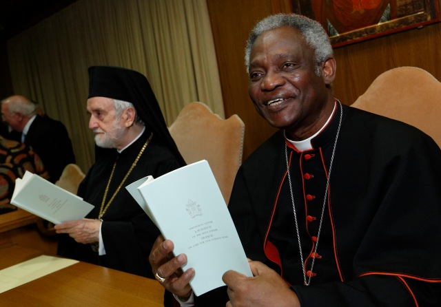 Cardinal Peter Turkson, president of the Pontifical Council for Justice and Peace, and Orthodox Metropolitan John of Pergamon, hold copies of Pope Francis' encyclical on the environment before a news conference at the Vatican June 18. (CNS/Paul Haring)