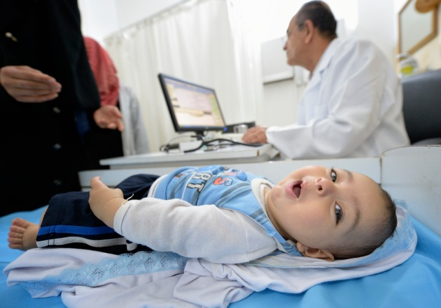 A baby looks around while the mother talks to a doctor in Gaza City.(CNS file/Paul Jeffrey)