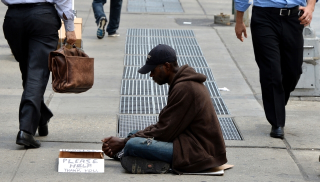 A homeless man sits on a sidewalk in New York City in this 2014 file photo. (CNS/EPA)