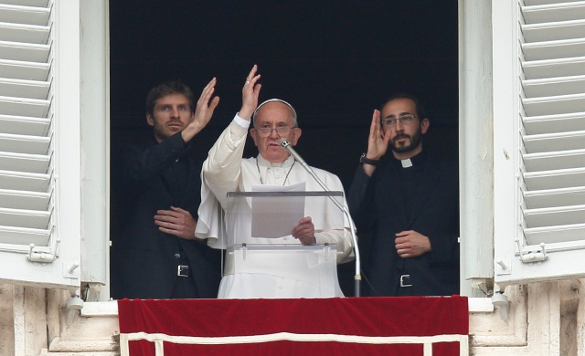 Pope Francis and two newly ordained priests give a blessing from the window of the pope's studio at the Vatican in April. The priests and 17 others were ordained by the pope during a liturgy in St. Peter's Basilica that morning. (CNS/Paul Haring)
