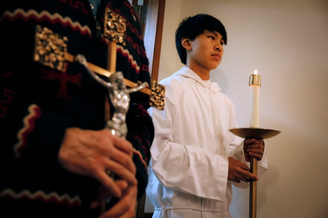 An altar server awaits the cue to process into the sanctuary at St. John by the Sea Church in Klawock on Prince of Wales Island in southeastern Alaska. (CNS/Nancy Wiechec)