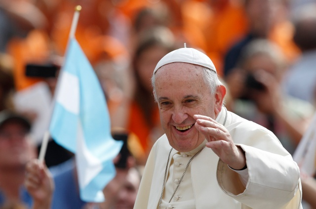 Pilgrim waves Argentina's flag as Pope Francis arrives to lead general audience in St. Peter's Square at Vatican