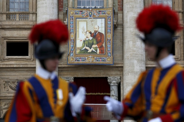A tapestry showing Louis and Zelie Martin, parents of St. Therese of Lisieux, hangs from a balcony as Pope Francis leads the Oct. 18 Mass for their canonization in St. Peter's Square at the Vatican. Pope Francis also canonized two others. (CNS/Reuters)