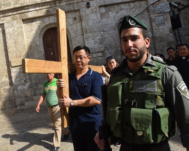 An Israeli border police officer stands near Catholic tourists from Indonesia as they carry a cross Oct. 18 on the Via Dolorosa in Jerusalem's Old City, near a site where several recent stabbings have taken place. (CNS/Debbie Hill)