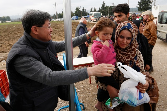 Cardinal Luis Antonio Tagle of Manila greets a family after giving them a food bag as refugees arrive at a transit camp in Idomeni, Greece, on the border of Macedonia Oct. 19. Thousands of refugees are arriving into Greece from Syria, Afghanistan, Iraq and other countries and then traveling further into Europe. (CNS/Paul Haring)