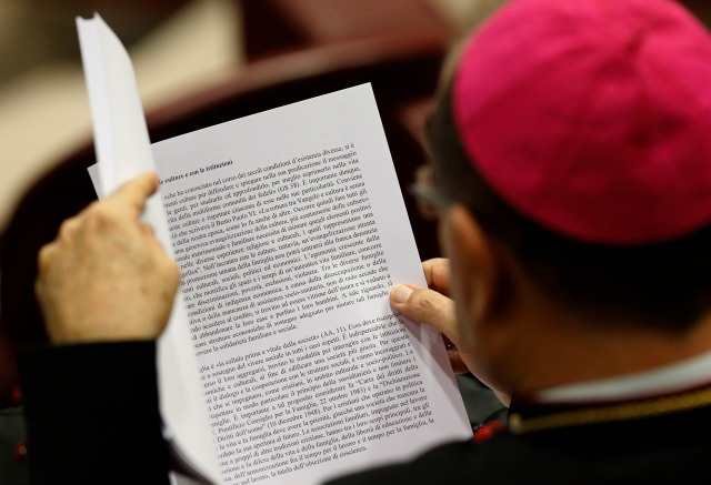 A bishop reads a draft in Italian of the final document of the Synod of Bishops on the family before a synod session at the Vatican Oct. 23. (CNS/Paul Haring)