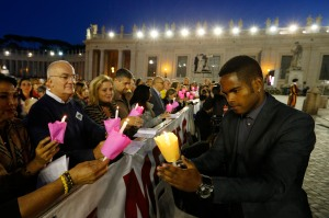 Juan Giron Ponz, a Cuban living in Italy, lights people's candles at a prayer vigil for the synod Oct. 3 in St. Peter's Square. (CNS/Paul Haring)