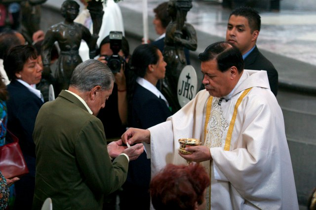 Cardinal Norberto Rivera Carrera of Mexico City distributes Communion during Mass in early May at Mexico City's Metropolitan Cathedral. (CNS/EPA)