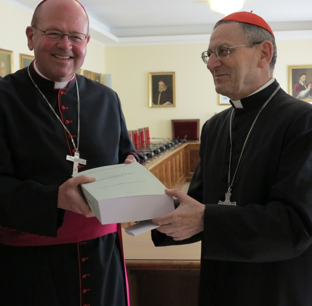 Bishop Carl A. Kemme of Wichita, Kan., presents Cardinal Angelo Amato, prefect of the Congregation for Saints' Causes, a report at the Vatican Nov. 9 detailing the life and heroic Christian virtues of Father Emil J. Kapaun, a Wichita priest and Army chaplain who died in a North Korean prison camp in 1951. (CNS/Cindy Wooden)