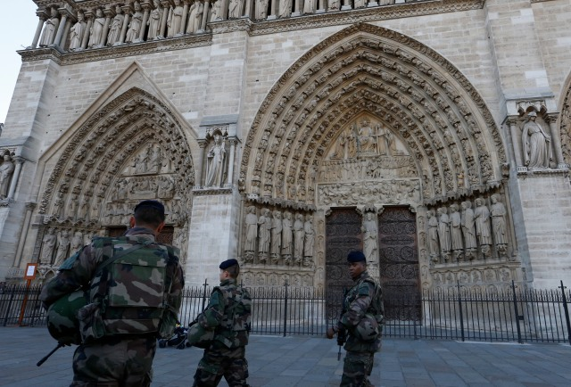 Soldiers pass the main entrance to Notre Dame cathedral in Paris in 2015 in the aftermath of terrorist attacks in Paris that killed 129 and injured 352. (CNS/Paul Haring)
