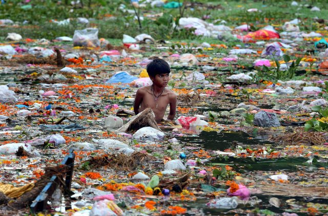 A young man collects items on Jawahar Lal Nehru Lake after a festival in Bhopal, India in 2014. (CNS/EPA)