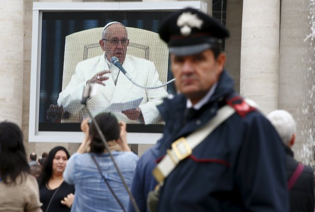 Pope Francis is seen on a video screen during his weekly general audience in St. Peter's Square Nov. 18. (CNS/Reuters)