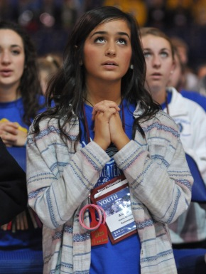 Alaina Sincich, a member of St. John Neumann Parish in Sunbury, Ohio, kneels in prayer Nov. 21 during the closing Mass of the National Catholic Youth Conference at Lucas Oil Stadium in Indianapolis. (CNS/Sean Gallagher, The Criterion)
