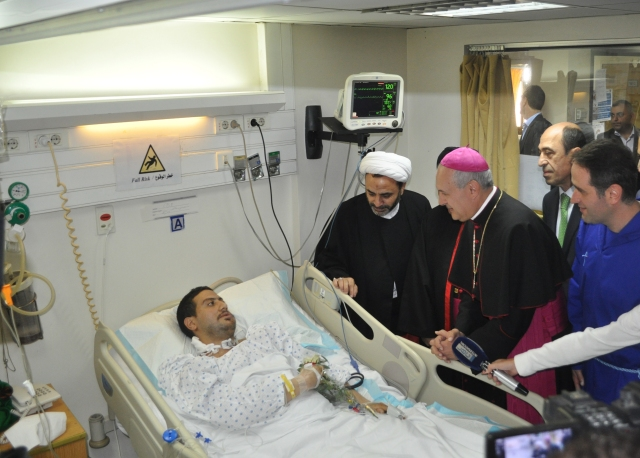 The Vatican's nuncio to Lebanon, Archbishop Gabriele Caccia, center, visits a hospitalized victim of the Nov. 12 twin suicide bombings in Beirut. Father Wissam Maalouf, founder and superior of Mission of Life, is at right. (CNS/courtesy Mission of Life, Lebanon)