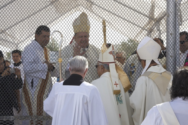 Bishop Ricardo Ramirez of Las Cruces, N.M., and Bishop Armando X. Ochoa of El Paso, Texas, foreground, share the sign of peace in 2011 with Bishop Renato Ascencio Leon of Ciudad Juarez, Mexico, through the fence separating Anapra, Mexico, on the outskirts of Ciudad Juarez, and Sunland Park, N.M., during an annual border Mass. Pope Francis will visit Ciudad Juarez in February. (CNS file/Christ Chavez, Rio Grande Catholic)