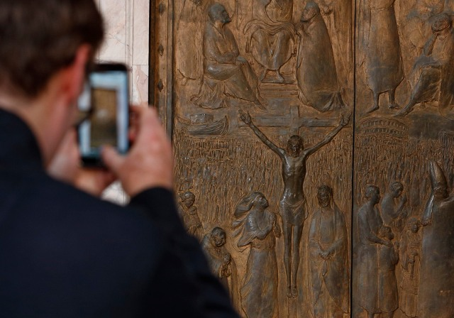 A visitor takes a photo of the Holy Door at the Basilica of St. Paul Outside the Walls in Rome. The Holy Doors of Rome's four papal basilicas will be opened during the Holy Year of Mercy, which begins Dec. 8. (CNS/Paul Haring)