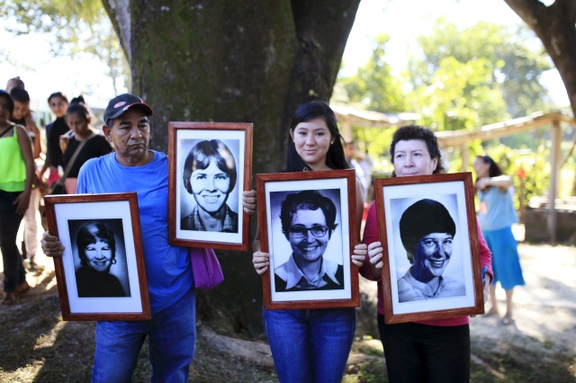 People hold pictures of four American churchwomen during a Dec. 2 memorial service to commemorate the 35th anniversary of their murder in the town of Santiago Nonualco, El Salvador. (CNS/Reuters)