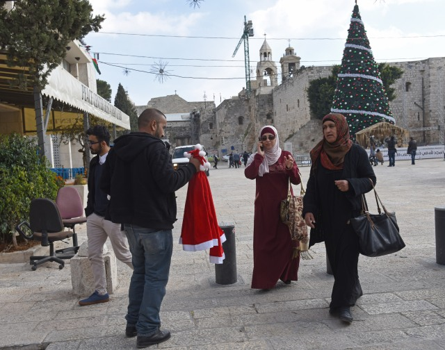 Jasan Zided, 38, from Hebron, West Bank, tries to sell Santa hats to local Palestinians in an empty Manger Square Dec. 15 in Bethlehem, West Bank. (CNS/Debbie Hill)