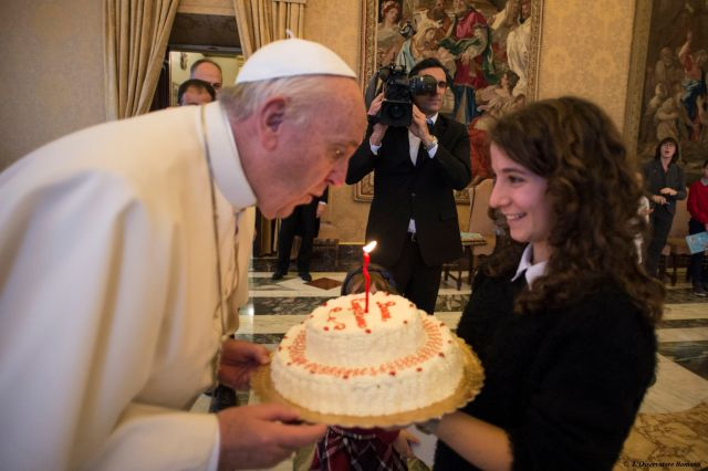 Pope Francis blows out the candle on a birthday cake presented by a young member of the Italian branch of Catholic Action during an audience with the group at the Vatican Dec. 17, the pope's 79th birthday. (CNS/L'Osservatore Romano)