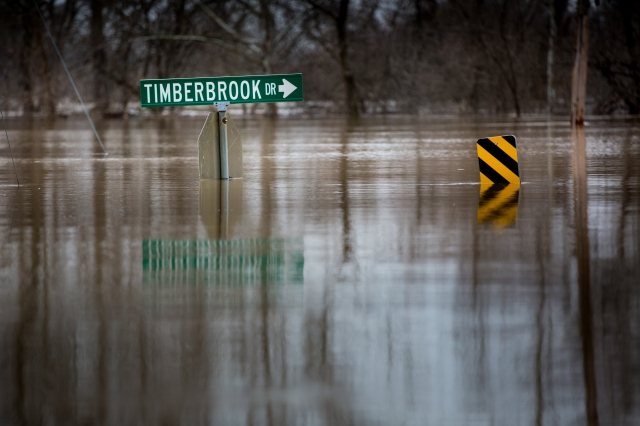 Street signs are seen under water Dec. 30 in Valley Park, Mo., as mandatory evacuations are underway where the river is expected to breach the levee. Gov. Jay Nixon activated the Missouri National Guard Dec. 22 in response to flooding after days of heavy rain and predicted record river levels. (CNS photo/Lisa Johnston, St. Louis Review)