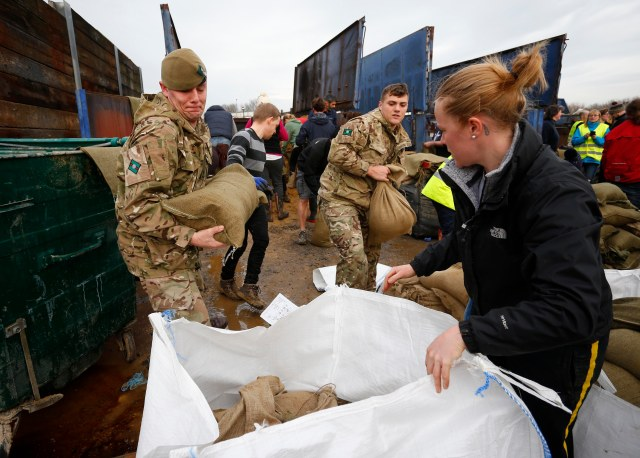 Local volunteers and the British Army fill sandbags Dec. 28 to stem floodwater in York, England. (CNS photo/Lindsey Parnaby, EPA)