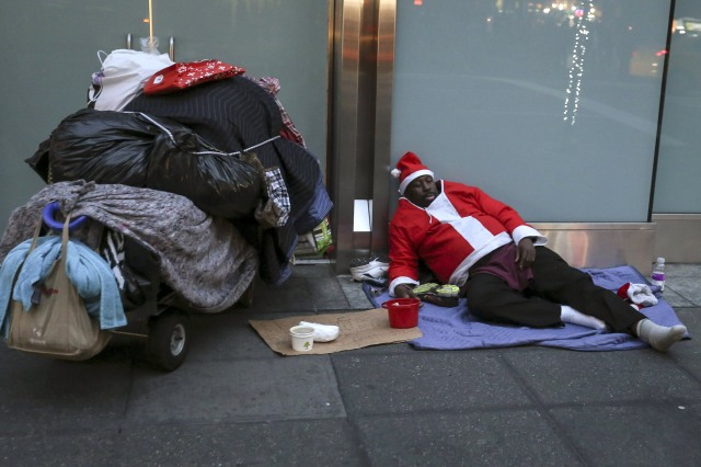 A homeless man dressed as Santa Claus sleeps on the ground during unseasonably warm weather on Christmas Eve in the Manhattan borough of New York. (CNS photo/Carlo Allegri, Reuters)