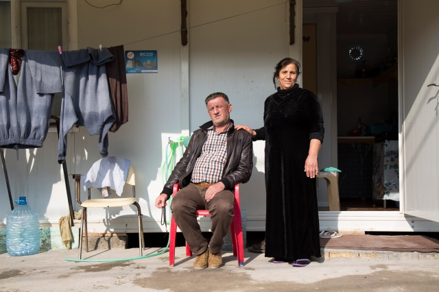 "Nabil Jelil Daud and his wife, Semira Ayup Miha, both from Qaraqosh, Iraq, pose in front of their trailer Dec. 16 at Ashti 2, a camp for internally displaced people in Irbil. ""It is very difficult to be happy on this Christmas because we are outside our homes,"" Daud said. (CNS photo/Oscar Durand)"