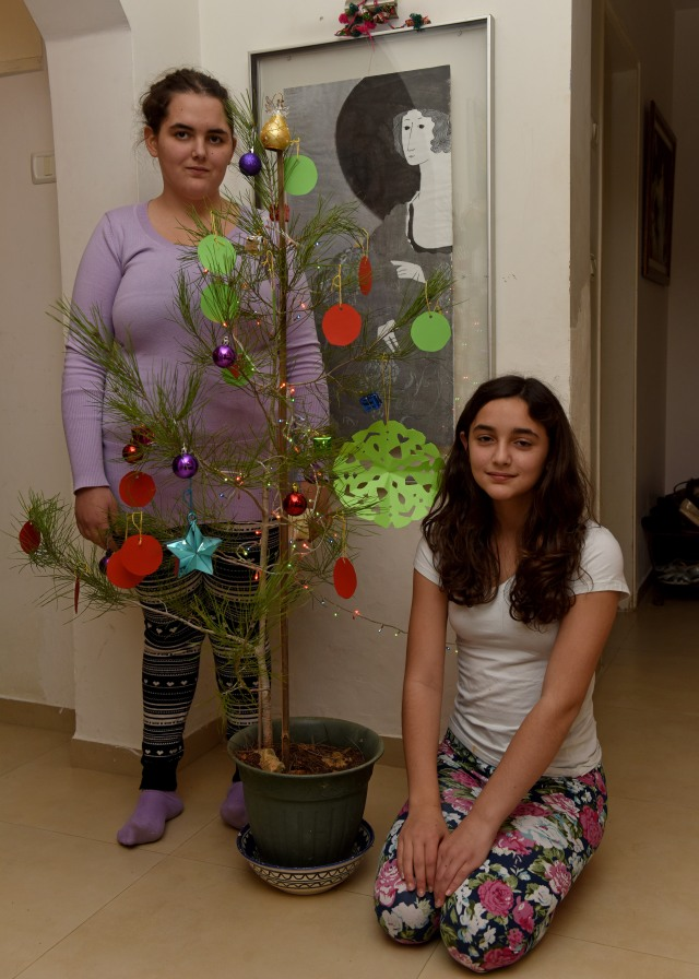 Israeli siblings Ella Bolton-Laor, 15, and Emily, 11, pose Dec. 27 alongside the Christmas tree at their house in Jerusalem. It is the second year Ella spearheaded the Christmas decorating, including in her bedroom. (CNS photo/Debbie Hill)