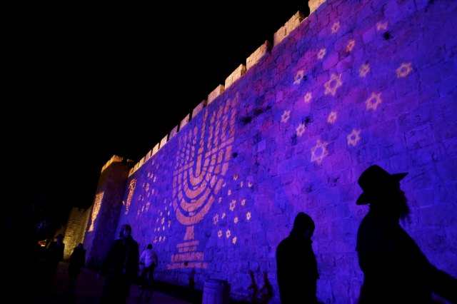 "People walk past an image of a Menorah projected on a wall surrounding the Old City of Jerusalem Dec. 8. Although Catholic are called to witness to their faith, the church ""neither conducts nor supports"" any institutional missionary initiative directed toward Jews, according to a new document from a Vatican commission. (CNS photo/Ammar Awad, Reuters)"