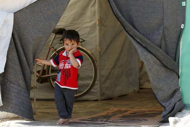 A Syrian refugee boy stands in front of his family's tent in late November at a camp in the Jordanian city of Mafraq, near the border with Syria. (CNS photo/Muhammad Hamed, Reuters)