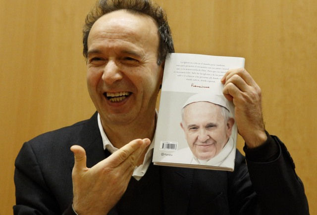 "Italian actor Roberto Benigni holds a copy of the book, ""The Name of God Is Mercy,"" during its presentation to journalists in Rome Jan. 12."