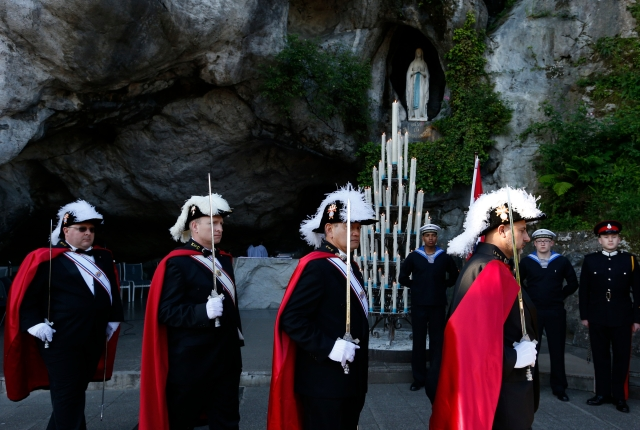 A color guard from the Knights of Columbus leaves after a Mass at the grotto at the Shrine of Our Lady of Lourdes in France in 2014. (CNS/Paul Haring)
