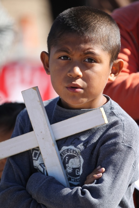 A boy holds a cross during Mass in 2014 in Sunland Park, N.M., at the Mexican border. (CNS/Bob Roller)
