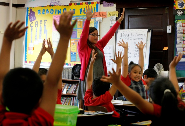 Maria Rodriguez exercises with her third-grade students during class at Maternity of the Blessed Virgin Mary School in Chicago. Rodriguez is part of the University of Notre Dame's Alliance for Catholic Education program. (CNS/Karen Callaway)
