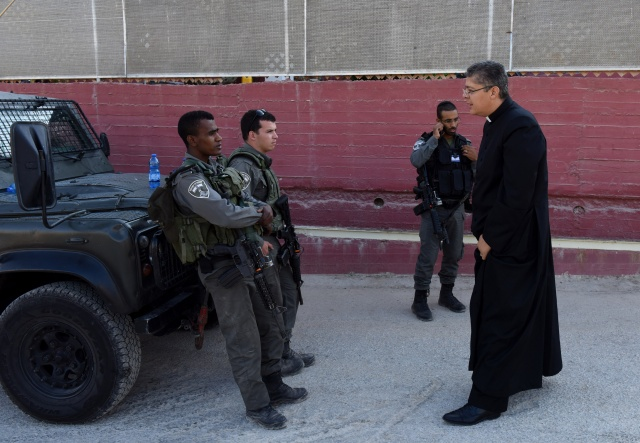 Father Aktham Hijazin of Beit Jalla, West Bank, tries to convince Israeli border police to let him pass to celebrate Mass Sept. 3. Israel is uprooting ancient Palestinian Christian-owned olive trees to make the way for the controversial separation barrier in the Cremisan Valley. (CNS/Debbie Hill)