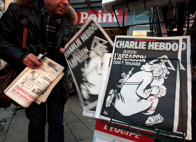 "A man takes a copy of the latest edition of French weekly magazine Charlie Hebdo with the headline ""One year on: the assassin is still out there,"" displayed Dec. 6 at a kiosk in Nice, France. Marking the first anniversary of when two Islamic extremists raided the magazine's offices and killed 12 people, the magazine featured a drawing of an angry God running with blood spattered on him and a machine gun slung over his back. (CNS/Reuters)"