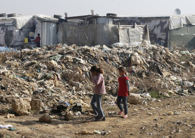 Syrian girls walk near garbage inside an informal refugee camp in Zahle, Lebanon. Lebanon continues to bear the brunt of absorbing massive numbers of refugees. (CNS/Reuters)