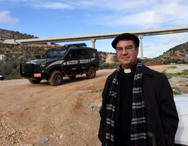Bishop Oscar Cantu of Las Cruces, N.M., stands in front of an Israeli border police jeep Jan. 10 near the Palestinian land in the Cremisan Valley in Beit Jalla, West Bank. (CNS/Debbie Hill)