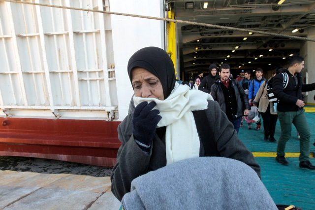 Refugees and migrants disembark from a ferry at the port of Piraeus, near Athens, Greece, Jan. 14. The ferry arrived carrying some 1,000 refugees and migrants who had landed the previous days on the Greek island of Lesbos, crossing from Turkey. (CNS/EPA)